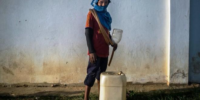Álvaro (nombre ficticio), un niño venezolano de 13 años, posa junto a sus herramientas de trabajo para el contrabando de gasolina: una garrafa y un embudo artesanal unido a un trozo de manguera, en Los Filúos, Paraguaipoa, Venezuela.