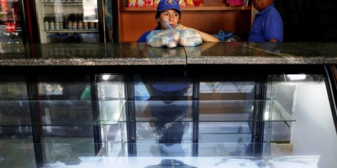 Una vendedora sostiene bolsas de pan mientras espera a los clientes en una panadería en Caracas el 17 de marzo de 2017. /  Marco Bello/Reuters